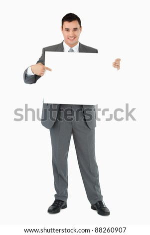 Businessman pointing at sign he is holding against a white background