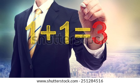 Businessman pointing at synergy concept 1+1=3 above the city - stock photo