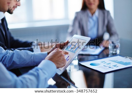 Businessman pointing at touchpad with data - stock photo