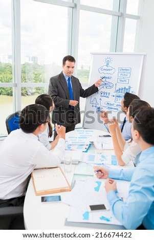 Businessman pointing at whiteboard while explaining some idea to his colleagues - stock photo