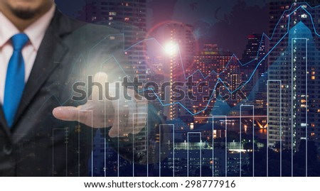 Businessman pointing or touching on Trading graph on the cityscape at night and world map background,Business financial concept - stock photo