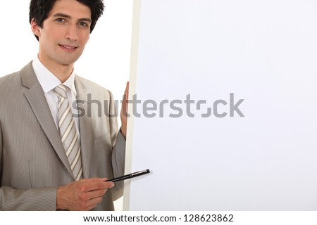 Businessman pointing to a blank flip chart - stock photo