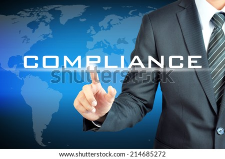 Businessman pointing to COMPLIANCE word on virtual screen - stock photo
