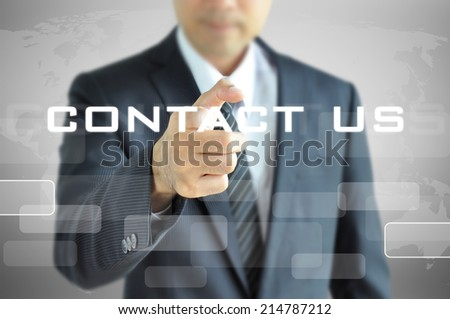 Businessman pointing to CONTACT US sign on virtual screen - stock photo