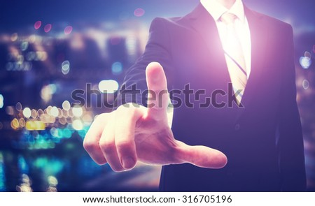 Businessman pointing to something on a blurred city background - stock photo