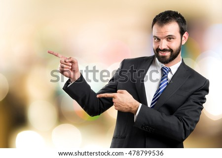 Businessman pointing to the side on unfocused background