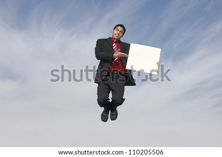 Businessman pointing while showing placard in midair - stock photo