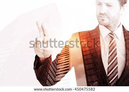 Businessman pointing with his finger against low angle view of skyscrapers