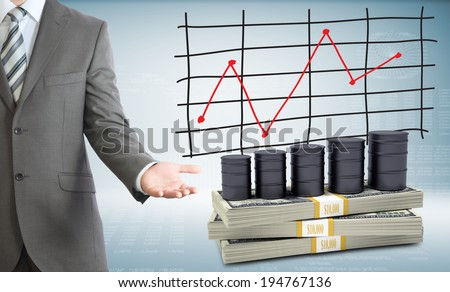 Businessman points hand on barrels oil and money. Schedule of price increases in background - stock photo