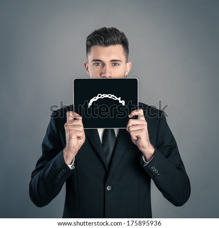 Businessman portrait against dark background with sad face on tablet. Conceptual image. - stock photo