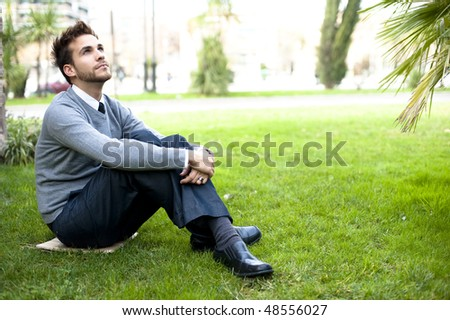 Businessman portrait in green park - stock photo