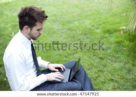Businessman portrait using laptop in park - stock photo