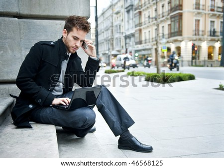 Businessman portrait with laptop and mobile phone