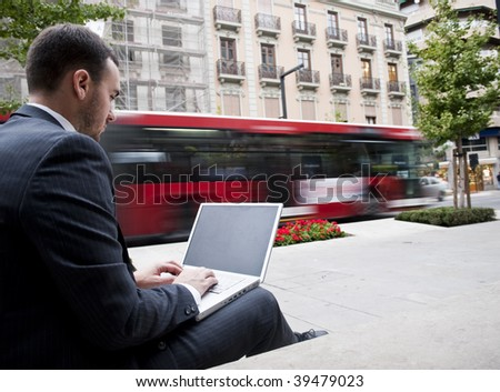 Businessman portrait with laptop in blurred urban background - stock photo