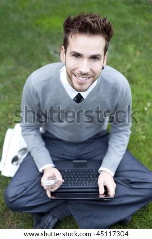 Businessman portrait with laptop (piercing in left ear) - stock photo