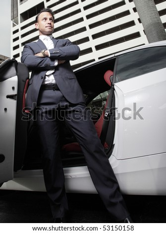 Businessman posing by a car