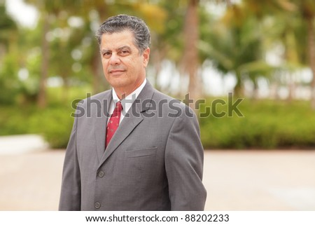 Businessman posing in a park setting - stock photo