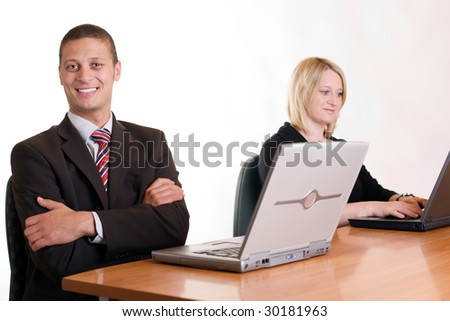 Businessman posing in office with colleague in background