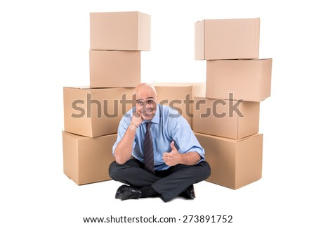 Businessman posing near a stack of cardboard boxes - stock photo