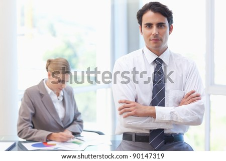 Businessman posing while his colleague is working in a meeting room - stock photo