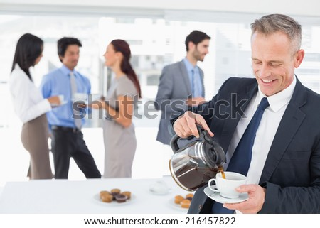 Businessman pouring himself some coffee in work - stock photo