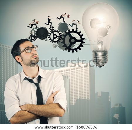 Businessman powering a big idea with a gear system - stock photo
