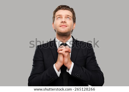 Businessman praying. Thoughtful young man in formalwear holding hands clasped and fingers crossed while standing against grey background - stock photo