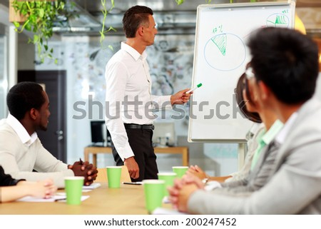 Businessman presenting a new strategy to his colleagues - stock photo