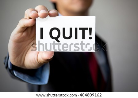 Businessman presenting 'I Quit' word on white card. - stock photo
