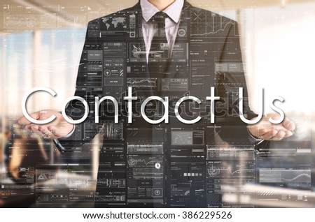 Businessman presenting text Contact Us on virtual screen. He is in the office - stock photo