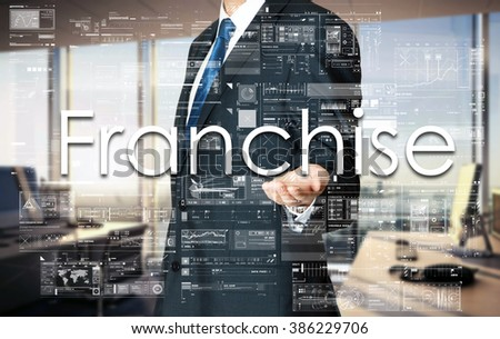 Businessman presenting text Franchise on virtual screen. He is in the office - stock photo