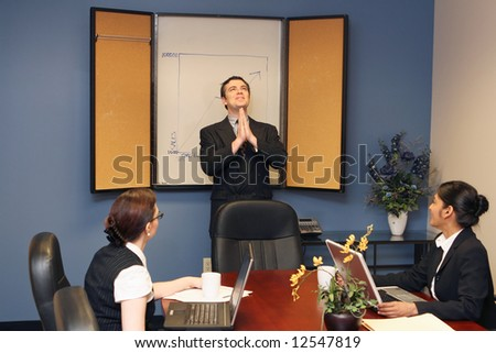 Businessman presenting to his colleagues staring up at the ceiling with his hands joined in prayer - stock photo