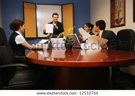 Businessman presenting to two businesswomen and one businessman.  The presenter is holding a piece of paper and smiling. - stock photo