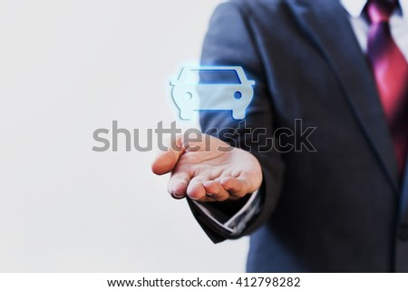 Businessman presenting virtual car on his palm of hand - car concept - stock photo