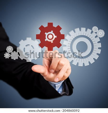 businessman pressing a cog wheel to keep the system running - stock photo