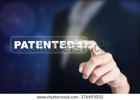 Businessman pressing a PATENTED concept button. Can be used in advertising. - stock photo