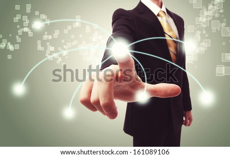 Businessman pressing a technology button on vintage green background - stock photo