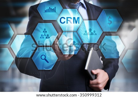 Businessman pressing button on touch screen interface and select CRM. busines concept.   - stock photo