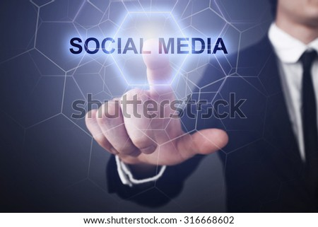 "Businessman pressing button on touch screen interface and select ""social media""."
