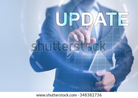 Businessman pressing button on touch screen interface and select Update. Business, internet, technology concept.