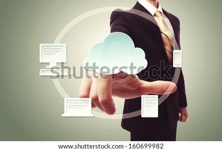 Businessman pressing cloud icon with devices over vintage green background - stock photo