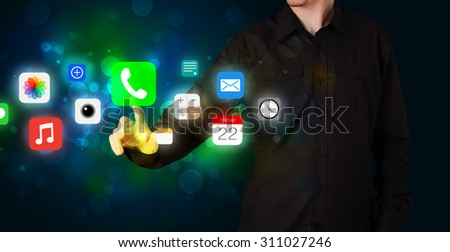 Businessman pressing colorful mobile app icons with bokeh background - stock photo