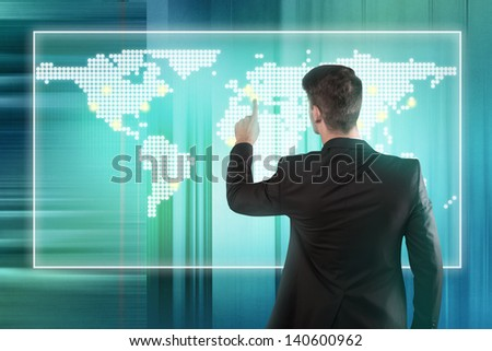 Businessman pressing location on a world map on screen - stock photo