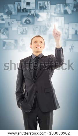 Businessman pressing  modern buttons with business images on a virtual background - stock photo