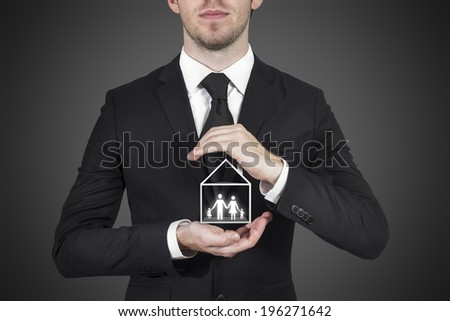 businessman protecting family standing in house with hands - stock photo
