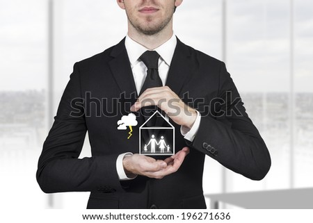 businessman protecting family standing in house with hands storm - stock photo