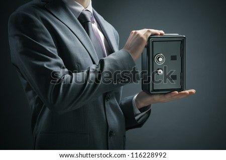 Businessman protecting his savings in the safe - stock photo