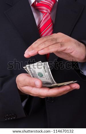 Businessman protecting, saving money between two hands. - stock photo