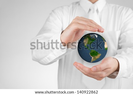 Businessman protecting the Earth. Sustainable responsible business, eco-friendly business, global business concepts. Move heaven and earth idiom. Map texture by NASA.