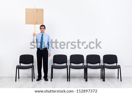 Businessman protesting alone with a placard - fighting for lost causes concept - stock photo